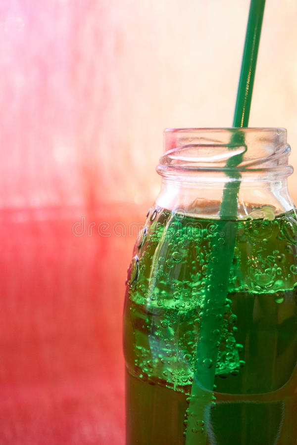 Top part of the bottle with soda mineral aerated water. In green color. with drinking straw and ice cubes royalty free stock photo