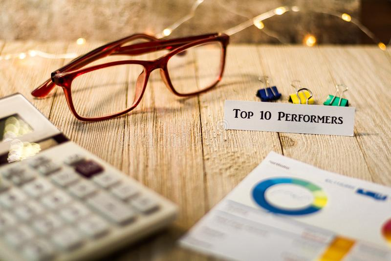 Top 10 Performers financial motivational concept. Financial motivational concept with charts and graphs and calculator on wooden board and festive lights stock photos