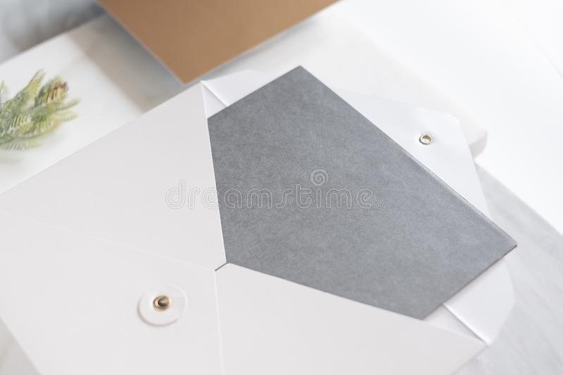 Top perspective view of blank grey card in white envelop with pine leaf on two layer step of marble table top.Mock up template for. Display of design,modern royalty free stock photos
