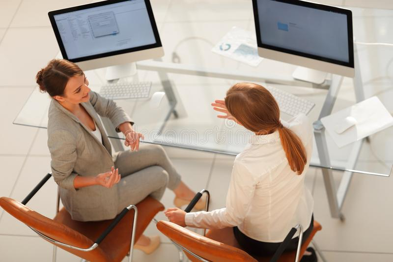 View from the top rear.business woman talking with a colleague sitting near the desktop stock photos