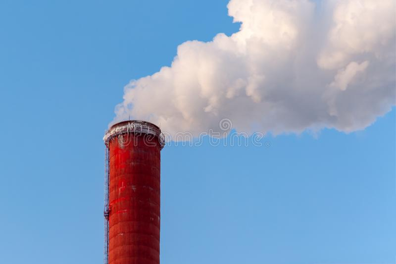 Top of the red chimney of a power station against a blue sky, cl stock photos
