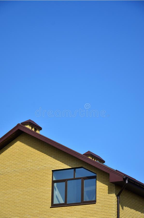 The top of a residential building of yellow brick. With a brown roof and plastic windows against a clear blue sky. The concept of roofing or exterior decoration royalty free stock photos