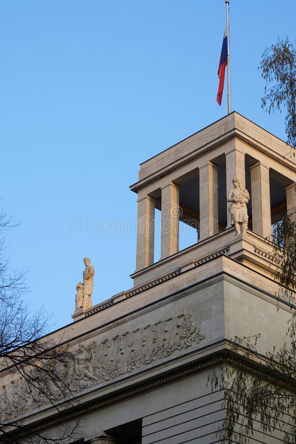 Top of Russian Federation Embassy building. Berlin, Germany - April 14, 2018: Top of Russian Federation Embassy building with flag, statues and USSR coat of arms stock photo