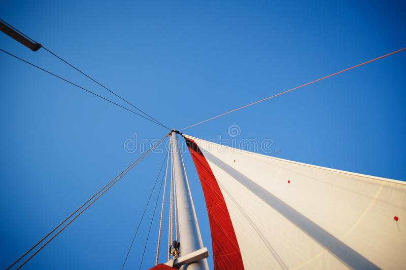 Top of the sailboat, mast head, sail and nautical rope yacht detail. Yachting, marine background.  stock photos