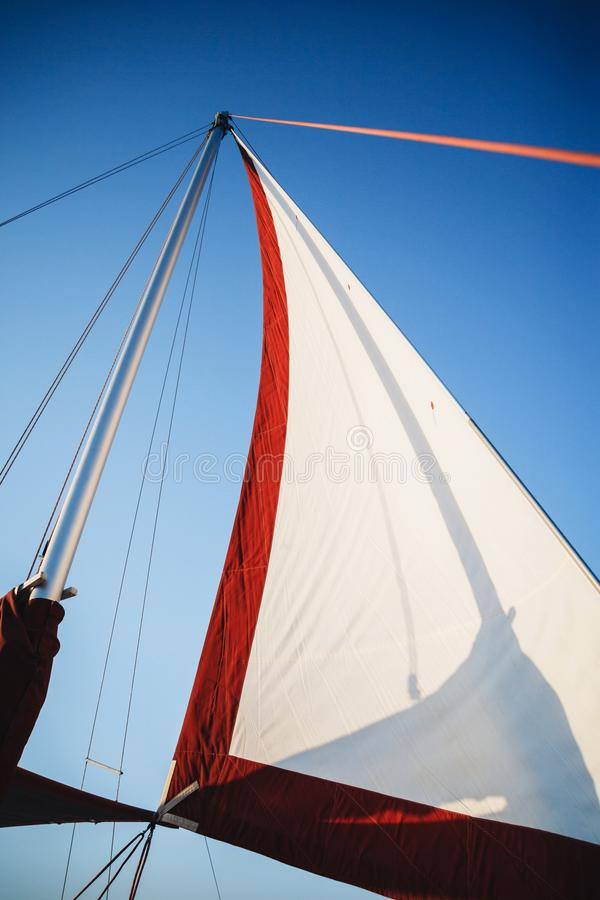Top of the sailboat, mast head, sail and nautical rope yacht detail. Yachting, marine background.  royalty free stock photography