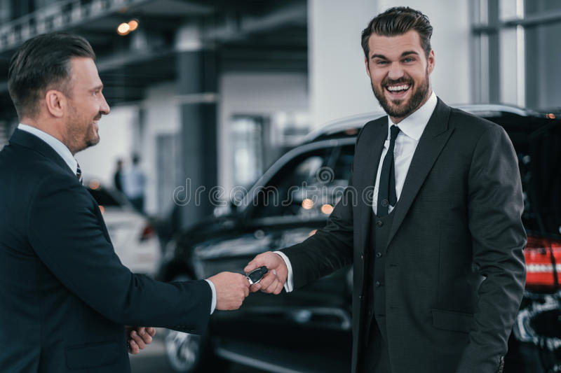Top sales manager and customer at dealership showroom royalty free stock photography