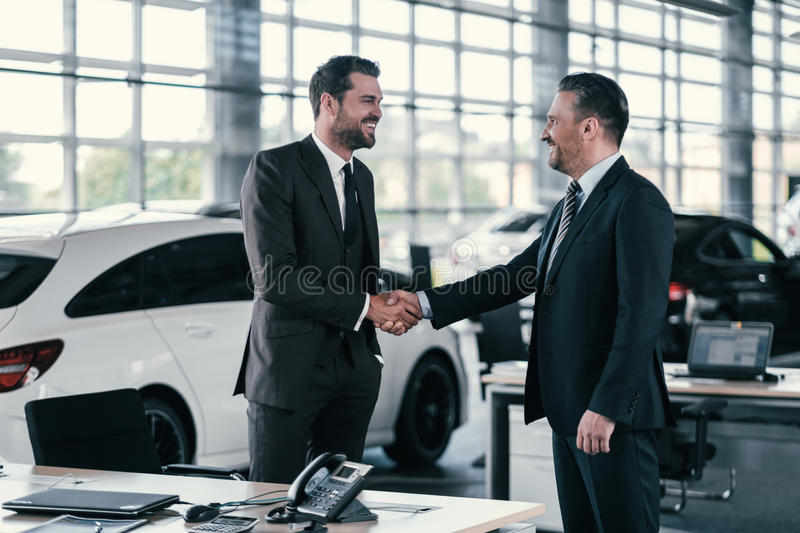 Top sales manager and customer at dealership showroom stock photography