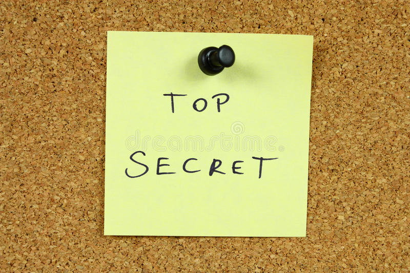 Top secret. Yellow small sticky note on an office cork bulletin board. Top secret - classified info stock image