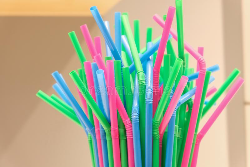 Top of several drinking straws made of plastic with different colors with blurred background. stock photography