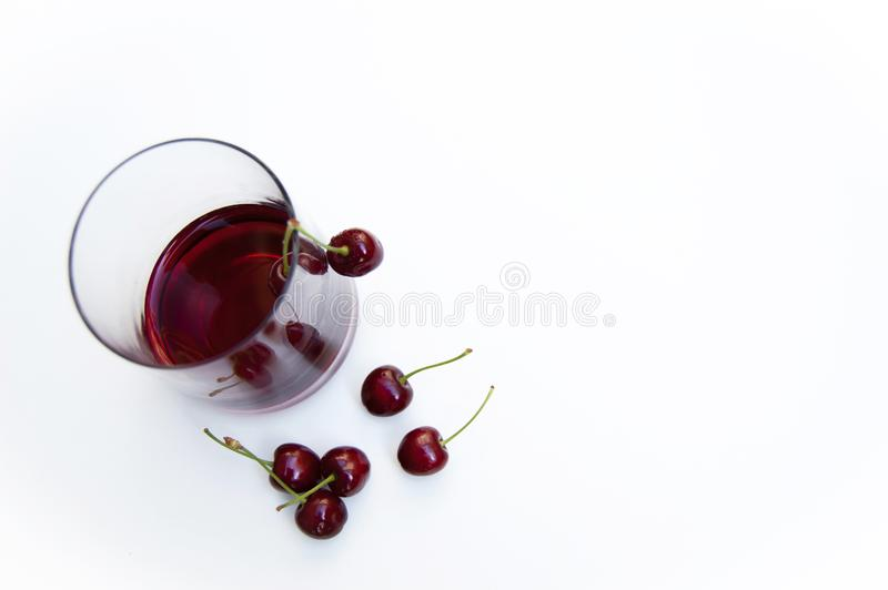 Top shot, close up of fresh sweet cherry with water drops, cherry juice in glass on white background, selective focus, royalty free stock photos