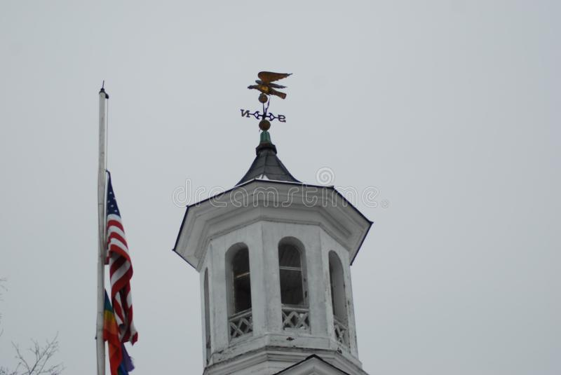 Top of small town public building next to American flag against a gray New England sky stock images