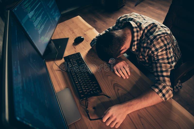 Top sobre la opinión de alto ángulo el suyo él buen tipo que duerme delante del especialista del genio del monitor trabajador en  imagen de archivo libre de regalías