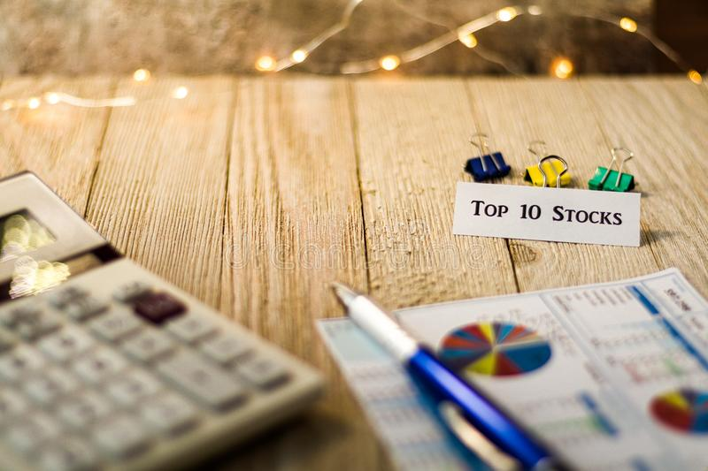 Top 10 stocks motivational concept on wooden board. Top 10 Stocks Investment Strategy motivational concept with charts and graphs and calculator on wooden board stock photos