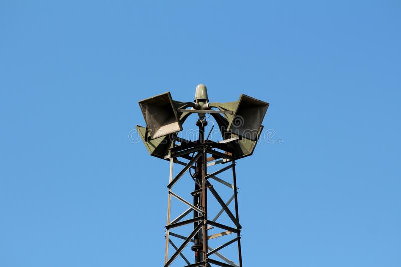 Top of tall metal structure holding four large public civil defence warning air sirens. On clear blue sky background stock photo