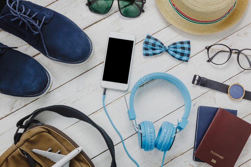 Top view accessoires to travel concept. Mobile phone listening music by headphone on wooden background.Man& x27;shoes,airplane,bag,passport,bow tie,watch stock photography