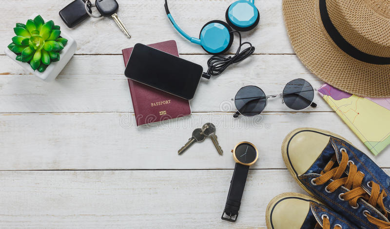 Top view accessoires to travel concept. Mobile phone listening music by headphone on wooden background.shoes,passport,watch,sunglasses and hat on wood table royalty free stock image