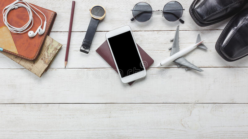 Top view accessoires to travel concept. White mobile phone and headphone on wooden background.airplane,map,passport,watch on wood table royalty free stock photos
