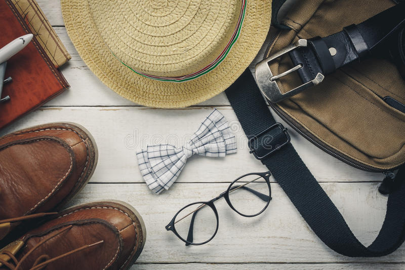 Top view accessoires to travel with man clothing. Concept. bow tie on wooden background.watch,eyeglasses,bag,hat,airplane,map on white wood table stock photography