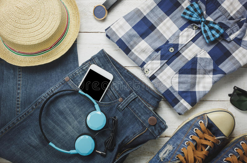 Top view accessoires to travel with man clothing . Top view accessoires to travel with man clothing concept.the essential shirt,jean,mobile phone ,headphone on stock image