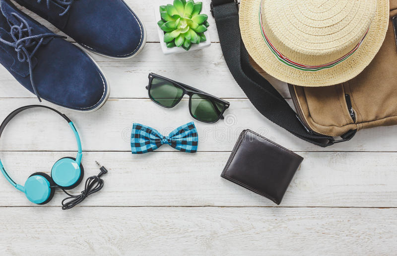 Top view accessoires to travel with man clothing. Top view accessoires to travel with man clothing concept. headphone on wooden background.bow tie,wallet stock photos