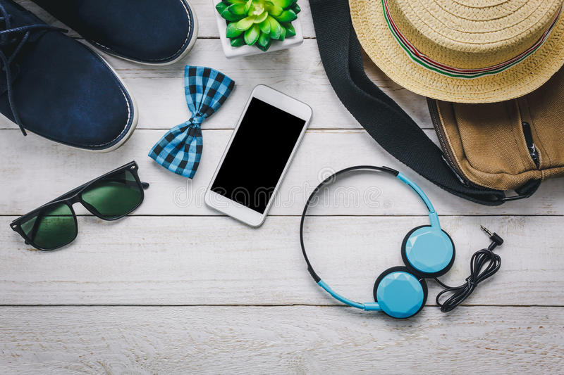 Top view accessoires to travel with man clothing. Top view accessoires to travel with man clothing concept. mobile phone and headphone on wooden background.bow royalty free stock photography
