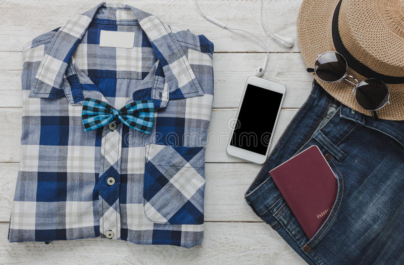 Top view accessoires to travel with man clothing . Top view accessoires to travel with man fashion clothing concept.shirt,jean,mobile phone listening music by royalty free stock images