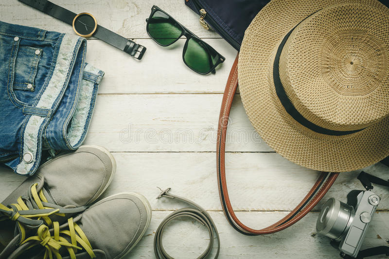 Top view accessoires to travel with women clothing. Top view accessoires to travel with women clothing concept.belt,bag,hat,camera,necklace,trousers,watch and stock photos
