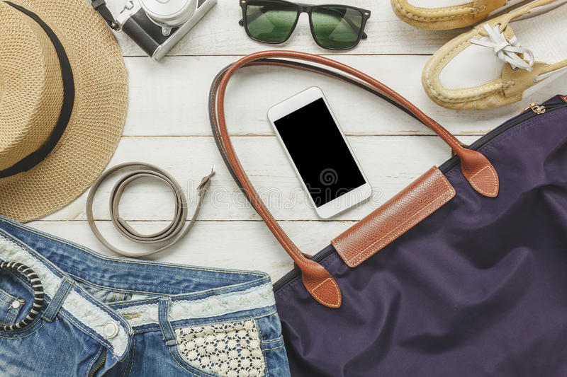 Top view accessoires to travel with women clothing. Concept.white mobilephone, belt,bag,hat,camera,necklace,trousers and sunglasses on white wood table stock photography