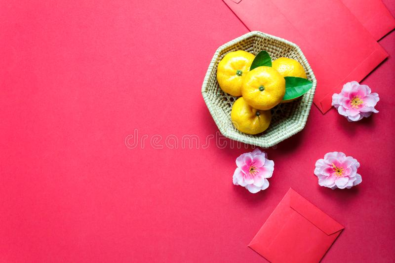 Top view accessories Chinese new year festival decorations.orange,leaf,wood basket,red packet,plum blossom on red background. royalty free stock photos