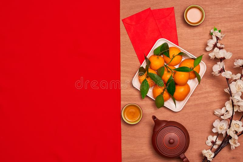 Top view accessories Chinese new year festival decorations.orange,leaf,wood basket,red packet,plum blossom on red background. stock image