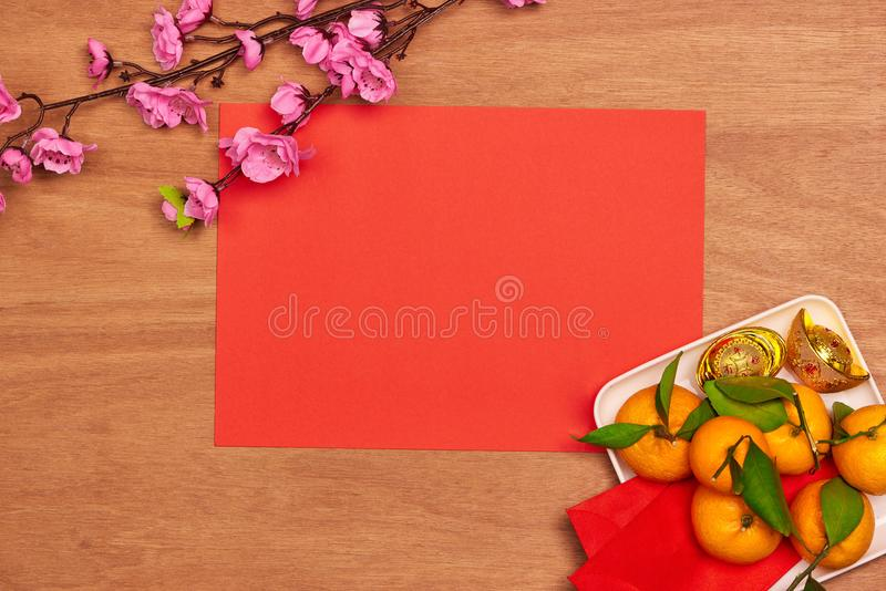 Top view accessories Chinese new year festival decorations.orange,leaf,wood basket,red packet,plum blossom on red background. royalty free stock image