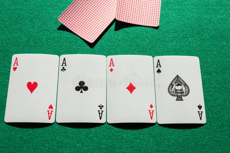 Top view of aces of poker deck, lined up, with covered cards, on green mat. Horizontal royalty free stock photo