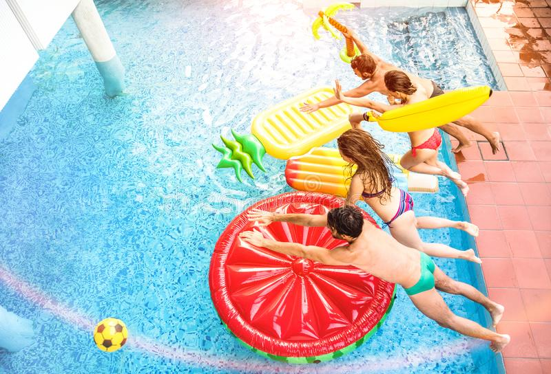 Top view of active friends jumping at swimming pool party - Vacation concept with happy guys and girls having fun in summer day. Top view of young people active royalty free stock photography