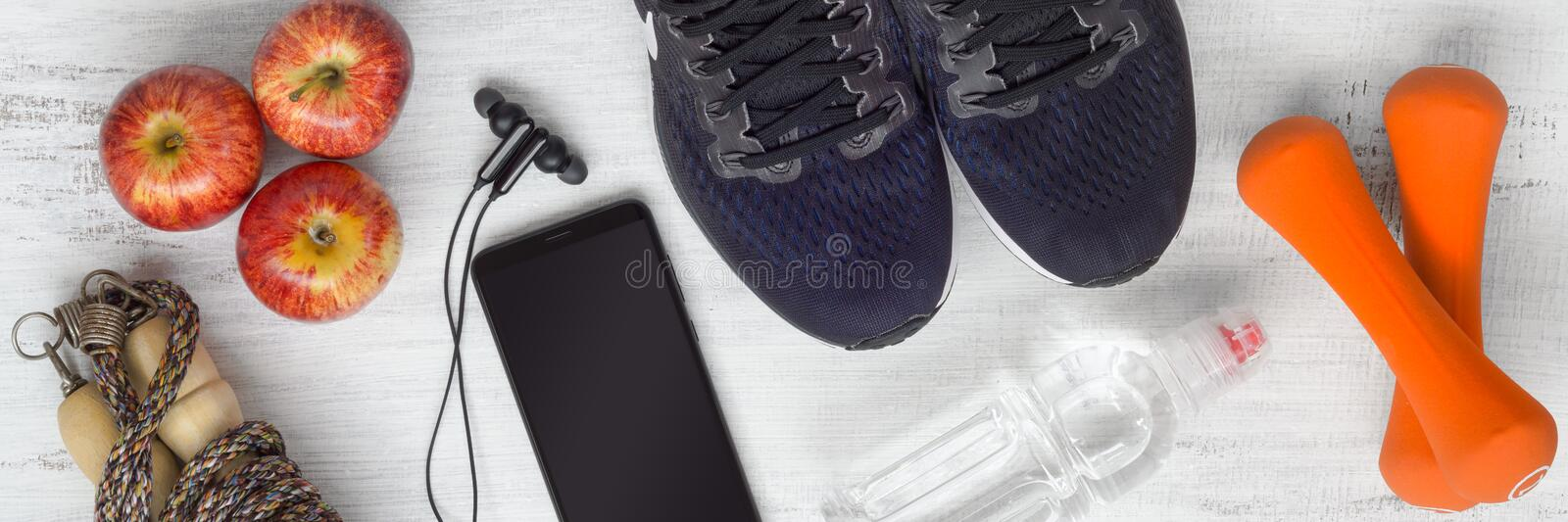Top view of Active healthy fitness and workout lifestyle background concept, sport equipments and fresh foods on grunge white wood royalty free stock photography