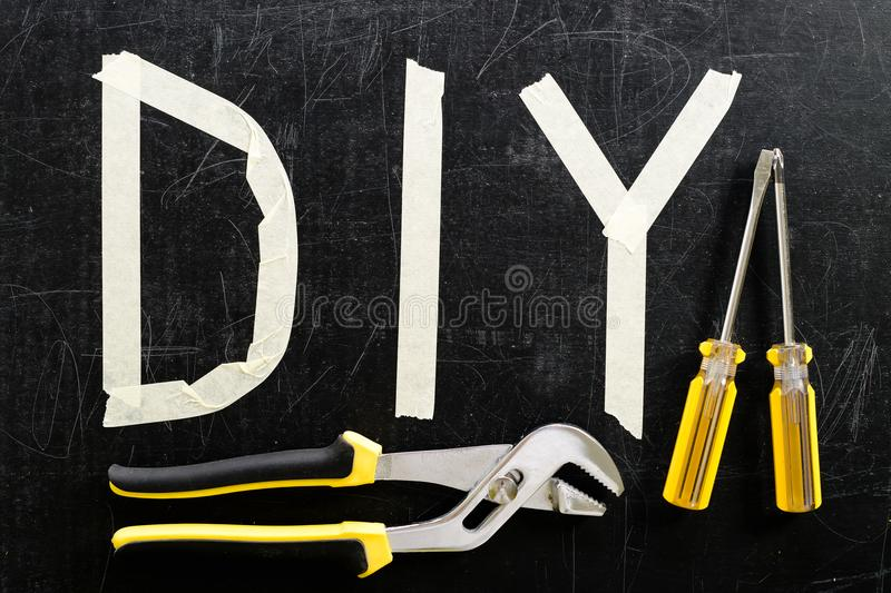Top view of adjustable wrench, screwdriver and word DIY made wit. H adhesive tape on dark background. Concept of do it yourself and manual work stock images