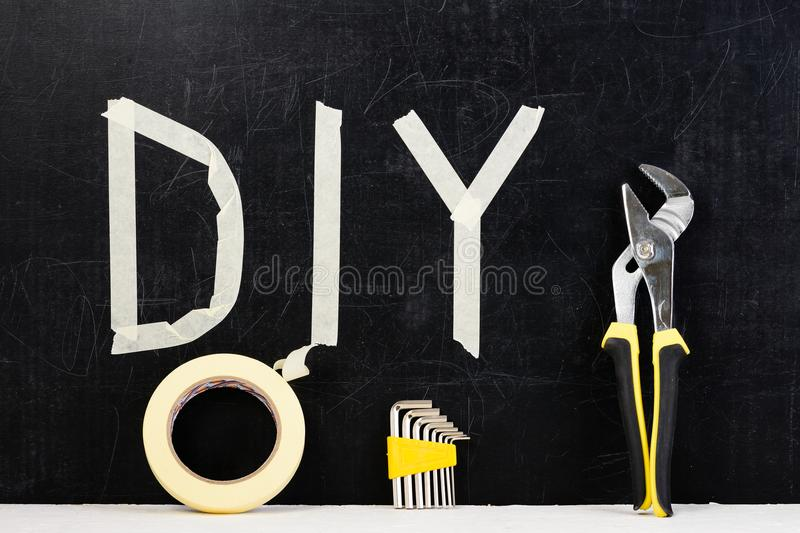Top view of adjustable wrench, sticky tape, hex key and word DIY made with adhesive tape on dark background. Concept of do it you. Rself and manual work royalty free stock images