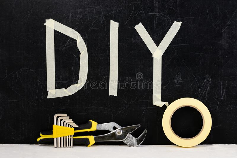 Top view of adjustable wrench, sticky tape, hex key and word DIY. Made with adhesive tape on dark background. Concept of do it yourself and manual work stock image
