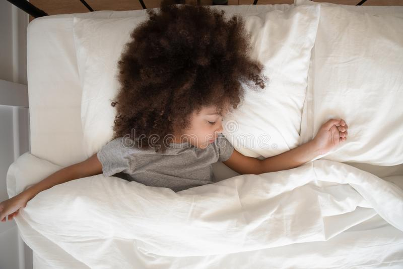 Top view adorable little african american kid girl sleeping alone. royalty free stock image