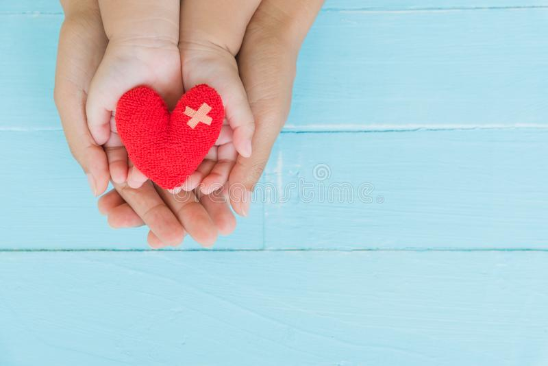 Top view of adult and child holding red heart in hands. Happy family relationships, Valentine`s day, Mother`s Day, Love and health care concept stock photography