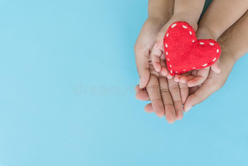 Top view of adult and child holding red heart in hands stock photography