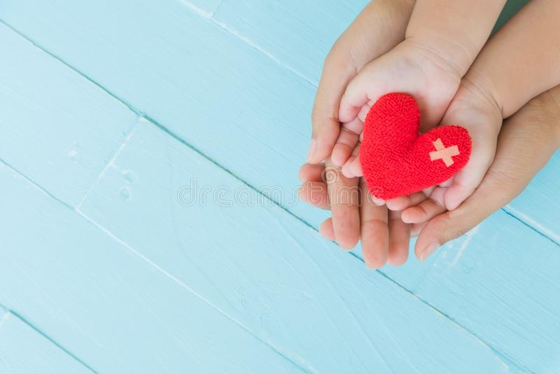 Top view of adult and child holding red heart in hands. Happy family relationships, Valentine`s day, Mother`s Day, Love and health care concept stock images
