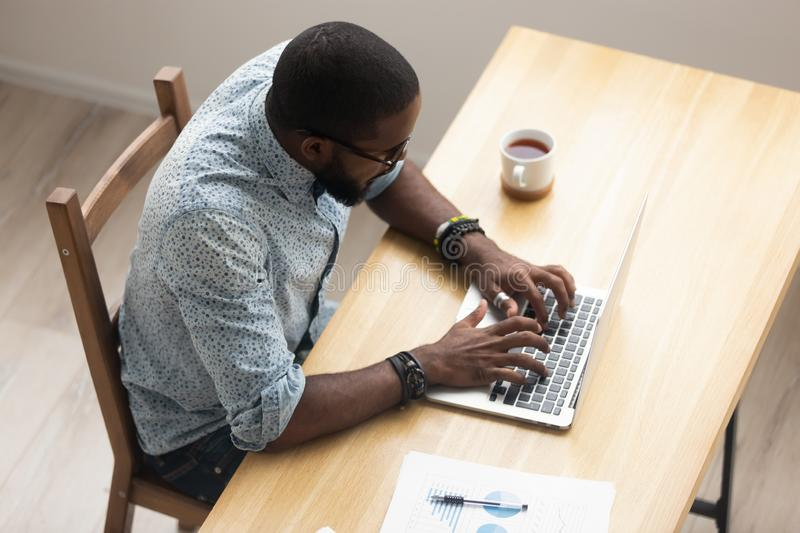 Top view African American employee working with laptop at office royalty free stock photography