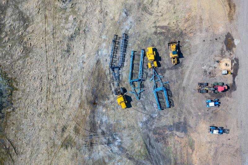 Top view on agricultural machinery near the hangar in the village for planting and harvesting. Three green tractors with large. Blue trailers for plowing the stock photo