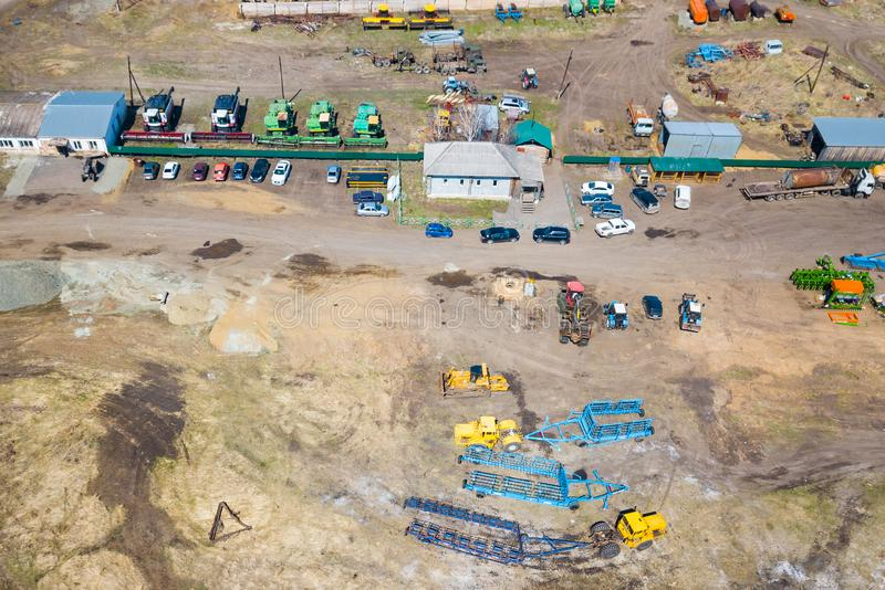 Top view on agricultural machinery near the hangar in the village for planting and harvesting. Tractor, plow, combine fuel truck. And truck in green and blue stock photo