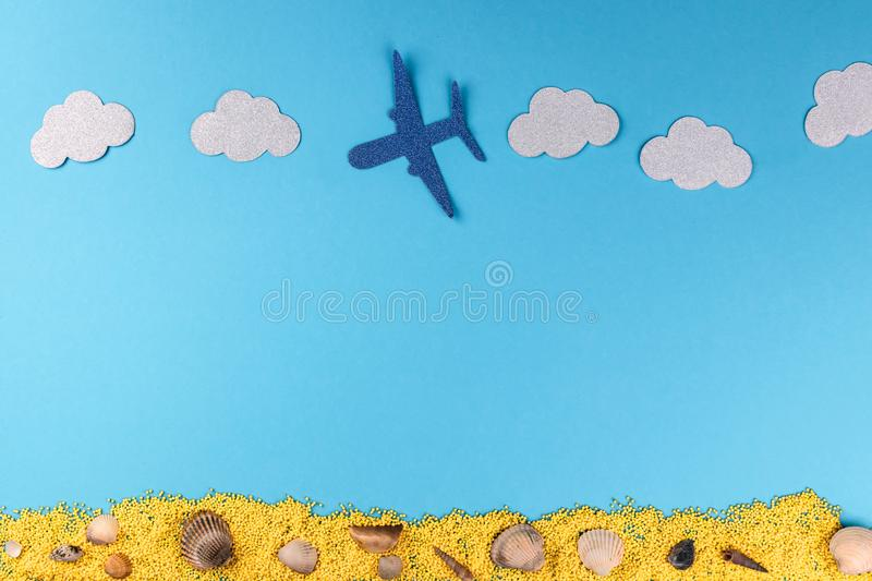 Top view of airplane flying on blue sky with white clouds above the yellow sand with shells. Flat lay minimal summer travel royalty free stock images