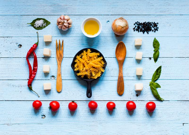 Top view of all the necessary food component to make a classic i. Talian pasta with tomato sauce with basil and olive oil stock photography
