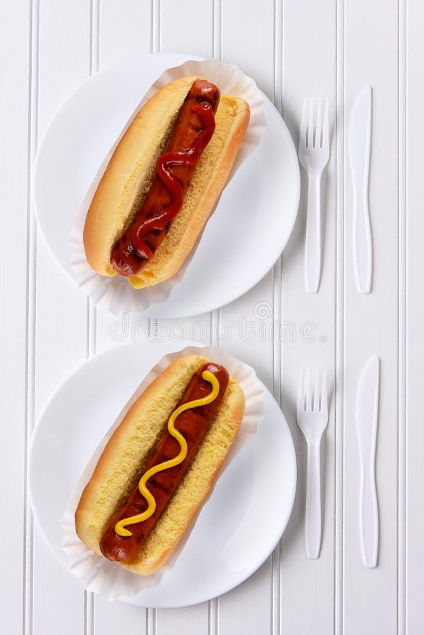 Top view of an all white place setting with hot dogs one with ketchup, one with mustard royalty free stock photography