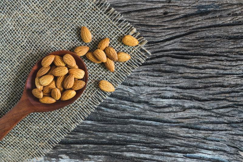 Top view almonds with wood spoon on dark wooden table background.  royalty free stock photography