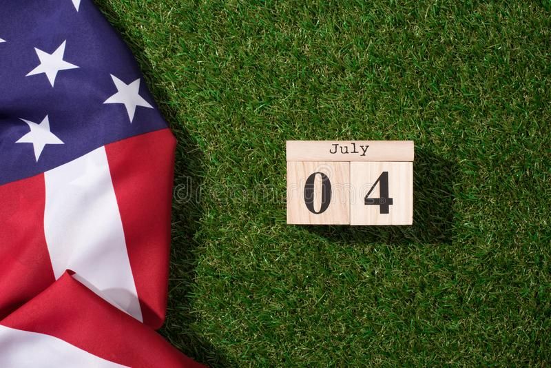 Top view of american flag and wooden calendar with 4th july date on green lawn, americas independence. Day concept stock image