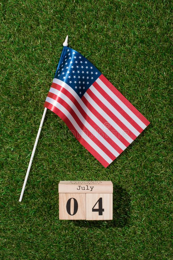Top view of american flagpole and wooden calendar with 4th july date on green grass, americas independence. Day concept stock photo